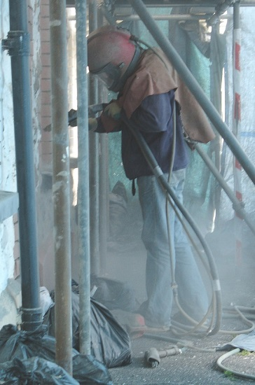 Sandblasting is a form of abrasive blast cleaning, as in this example where a stone wall is being cleaned